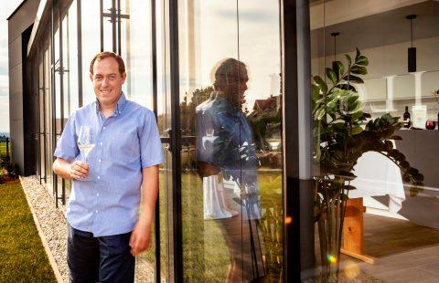 Stefan Gilg steht im Sonnenuntergang vor dem neuen Weinshop